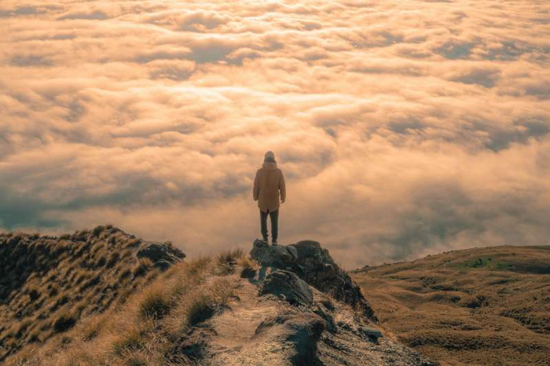 explorer on a mountain with clouds