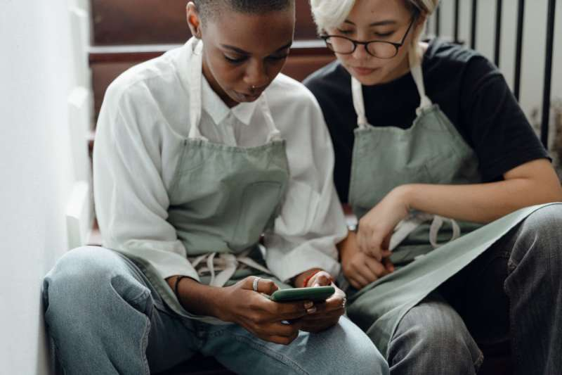 two ladies sat on a staircase wearing aprons looking at a mobile phone screen