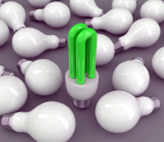 A green light-bulb amongst many other standard bulbs, showing an idea standing out amongst the rest